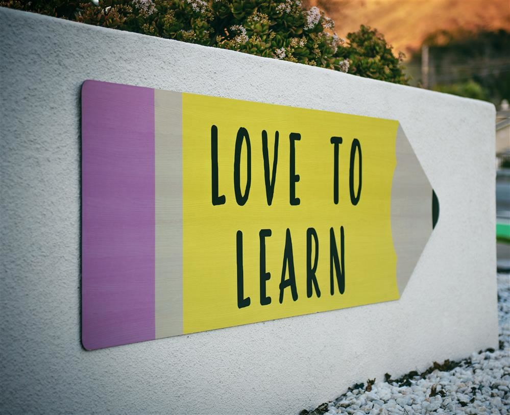 A sign with a Pencil on it stating Love to Learn.